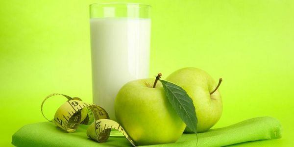 Glass of kefir, apples and measuring tape, on green background